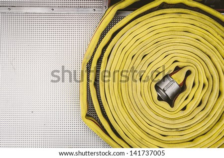Coiled yellow fire hose against a chrome, patterned surface in a fire engine