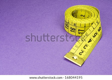 Coiled Yellow Measuring Tape on Purple Background Photo - stock photo