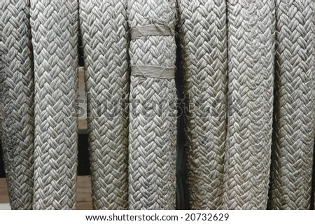 Coils of grey braided rope at the dock in close-up - stock photo