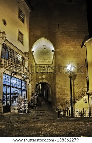 COIMBRA, PORTUGAL - DECEMBER 1: Entry to medieval city sector on December 1, 2012 in Coimbra, Portugal. Almedina gate in the wall (XI century) and souvenirs shop. - stock photo