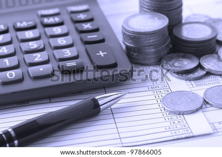 coin, a calculator, a pen on the business papers