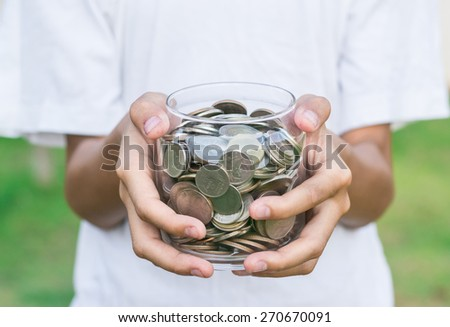 coin in grass bottle with boy hand - stock photo