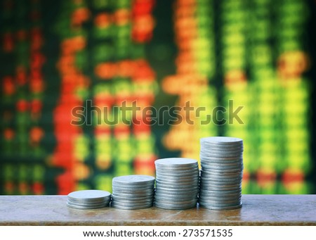 coin money  on wooden table over share of stock. money stack . - stock photo