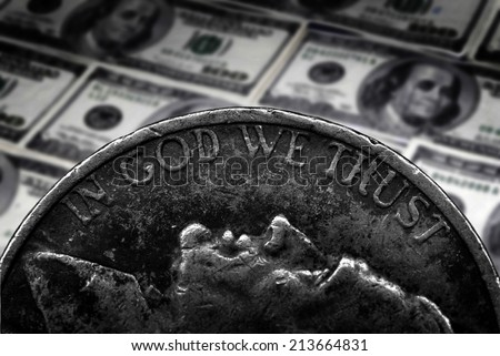Coin of Silver American Money with words In God We Trust over hundred dollar bills - stock photo