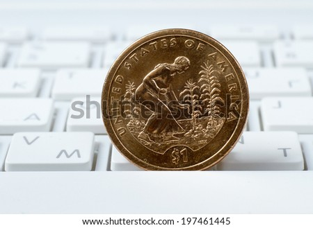 coin on a laptop keyboard - stock photo