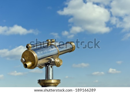 coin operated antique telesecope with brass and metal elements in front of a blue cloudy sky - stock photo