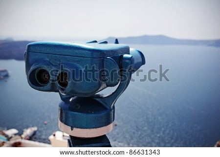 Coin operated binocular against harbor of Fira, Santorini island, Greece. - stock photo
