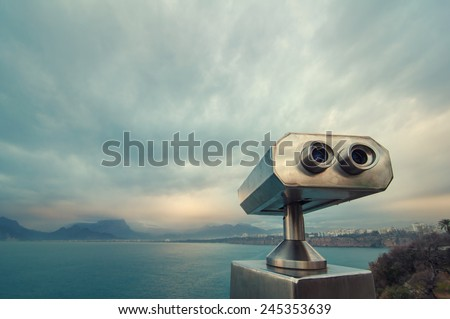 Coin Operated Binocular viewer next to the waterside promenade in Antalya looking out to the Bay and city. Landscape with beautiful cloudy sky, sea and mountains.. - stock photo