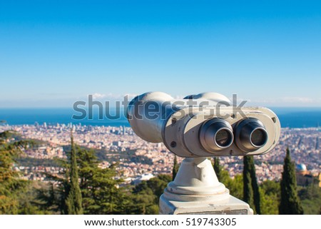 Coin operated binoculars and panoramic view of the city on a sunny day