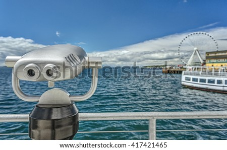 Coin Operated Binoculars Look out towards the Seattle Great Wheel on a Sunny Day - stock photo