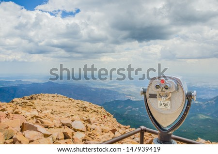 Coin-operated Binoculars on the Summit of Pikes Peak Mountain and Cloudy Sky - stock photo