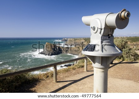 Coin operated telescope in a coastline viewpoint overlooking the ocean (Pay per view concept) - stock photo