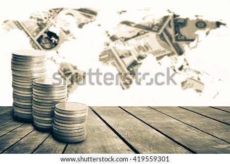 coin stack on old wooden floor with blur world map on pile of banknote background - stock photo