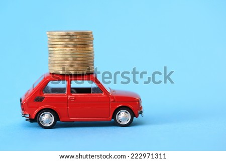 Coin stack on red miniature car - stock photo