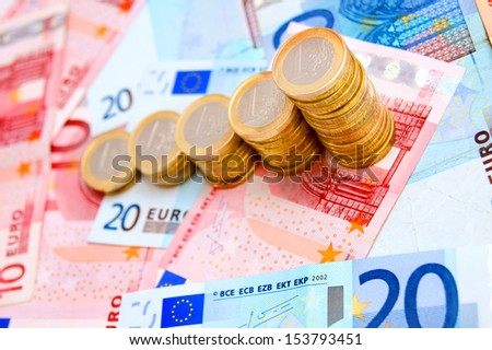 Coins against from banknotes - stock photo