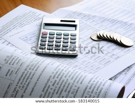 coins and calculator on business paper - stock photo