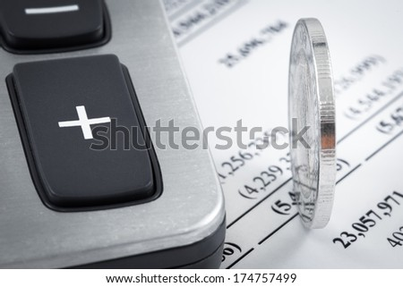 Coins and calculator on business report - stock photo