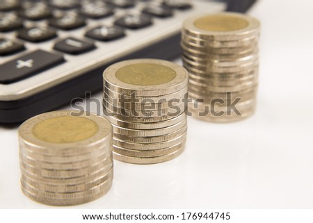 Coins and calculator with pen - stock photo