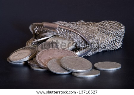 Coins and coin wallet against black background