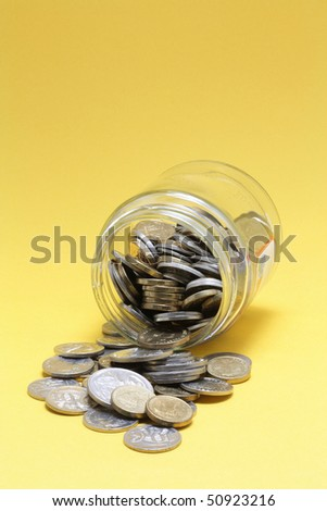 Coins and Glass Jar on Yellow Background