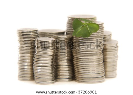 Coins and lucky clover. - stock photo