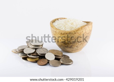 coins and white rice on a white background. The increase in the price of rice, the rising cost of rice, inflation, crisis, isolated - stock photo