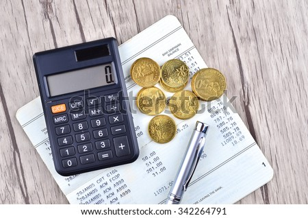 Coins, calculator and pen on bank account book - stock photo