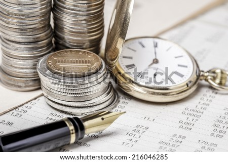 Coins, clock  and fountain pen on  a data table  - stock photo