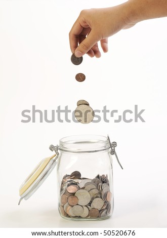 coins dropping in glass jar - stock photo