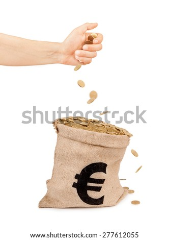 coins falling from hand into the bag with coins - stock photo