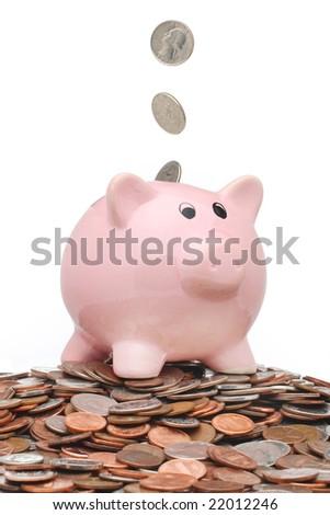 Coins falling into a piggy bank - stock photo
