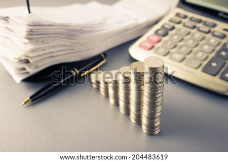 Coins heap stair as growing graph symbol on finance working desk