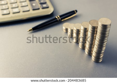 Coins heap stair as growing graph symbol on finance working desk - stock photo