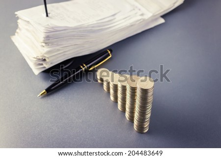 Coins heap stair as growing graph symbol with pen and receipts in paper nail - stock photo