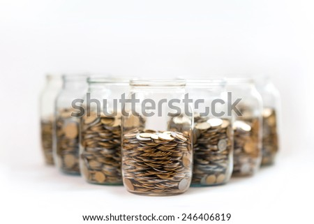 coins in a three glass jars against a white background - stock photo