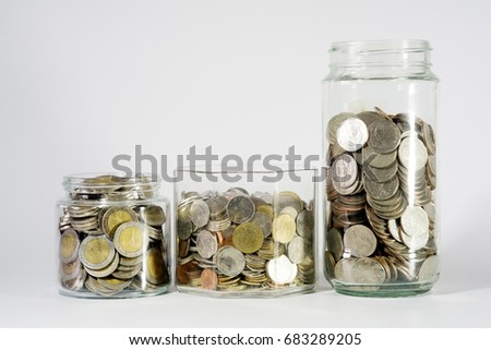 Coins in a three glass jars on white background