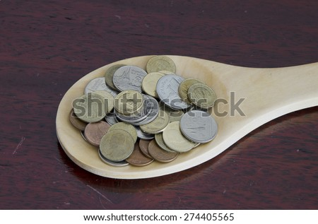 Coins in a wooden spoon on a dark wood background - stock photo