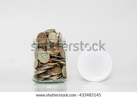 Coins in glass jar, and covered, with copy space on white background - stock photo