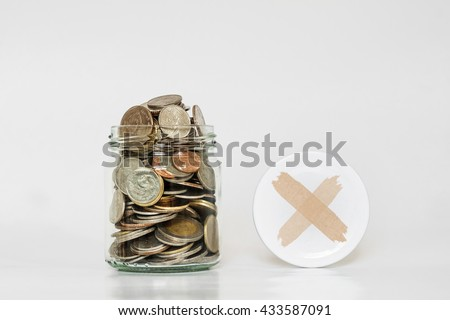 Coins in glass jar, and covered with cross symbol - stock photo