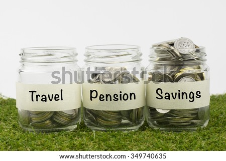Coins in glass jar contains coins for travel, pension and savings. financial concept. Selective focus and shallow depth of field - stock photo