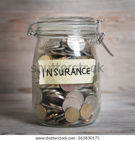 Coins in glass jar with insurance label, financial concept. Vintage wooden background with dramatic light. - stock photo