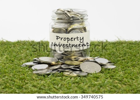 Coins in glass jar with property investment label, financial concept. Selective focus and shallow depth of field - stock photo