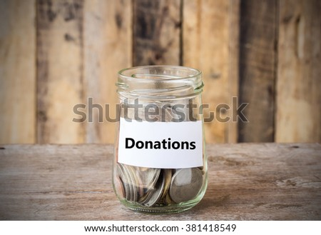 Coins in glass money jar with donations label, financial concept. Vintage wooden background