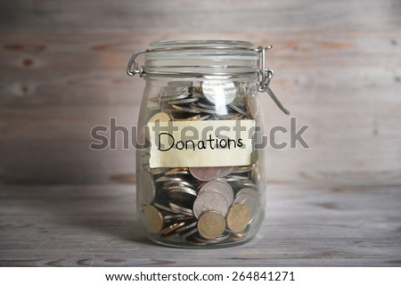Coins in glass money jar with donations label, financial concept. Vintage wooden background with dramatic light. - stock photo