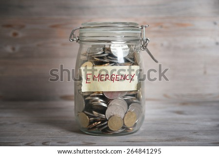 Coins in glass money jar with emergency label, financial concept. Vintage wooden background with dramatic light. - stock photo