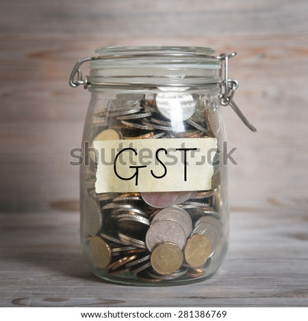 Coins in glass money jar with gst label, financial concept. Vintage wooden background with dramatic light. - stock photo