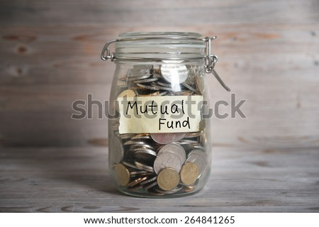 Coins in glass money jar with mutual fund label, financial concept. Vintage wooden background with dramatic light. - stock photo