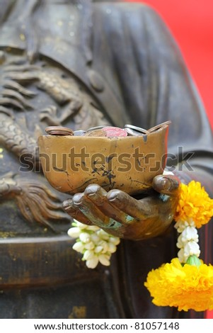 Coins in Hand of Chi Zing Eie , Chinese god of Wealthy. - stock photo