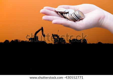 Coins in hands on Industry  silhouette Landscape background,Donation Investment Fund Financial Support Charity  Dividend Market Growth Home House Stock Trust Wealthy Giving Planned Accounting - stock photo