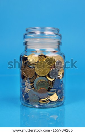 coins in jar on blue background - stock photo